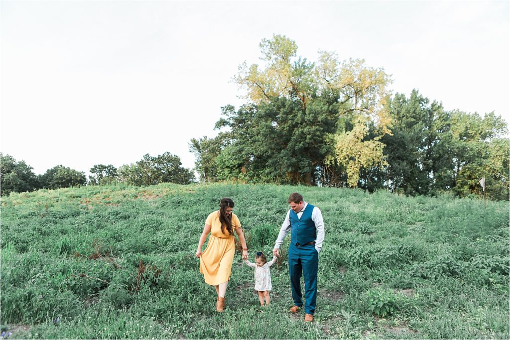 Mom Dad and toddler walking in field for family photos